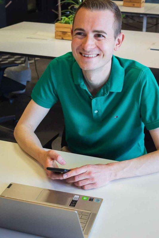Frederik Schafmeister vor dem Laptop mit Smartphone in der Hand