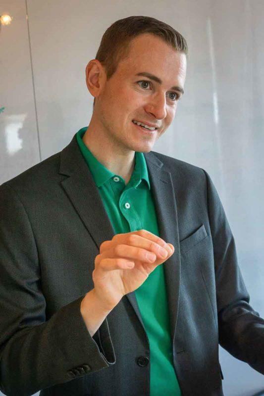 Frederik Schafmeister mit Jacket in Beratungsgespräch am erklären