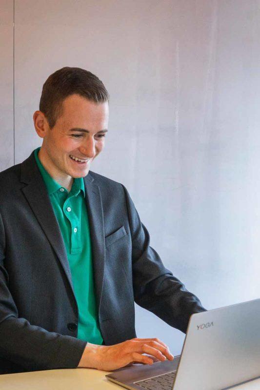 Frederik Schafmeister mit Jacket in Beratungsgespräch am Laptop stehend