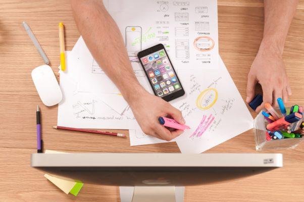 Kreativprozess: Schreibtisch mit Notizen, Textmarker, Computerbildschirm